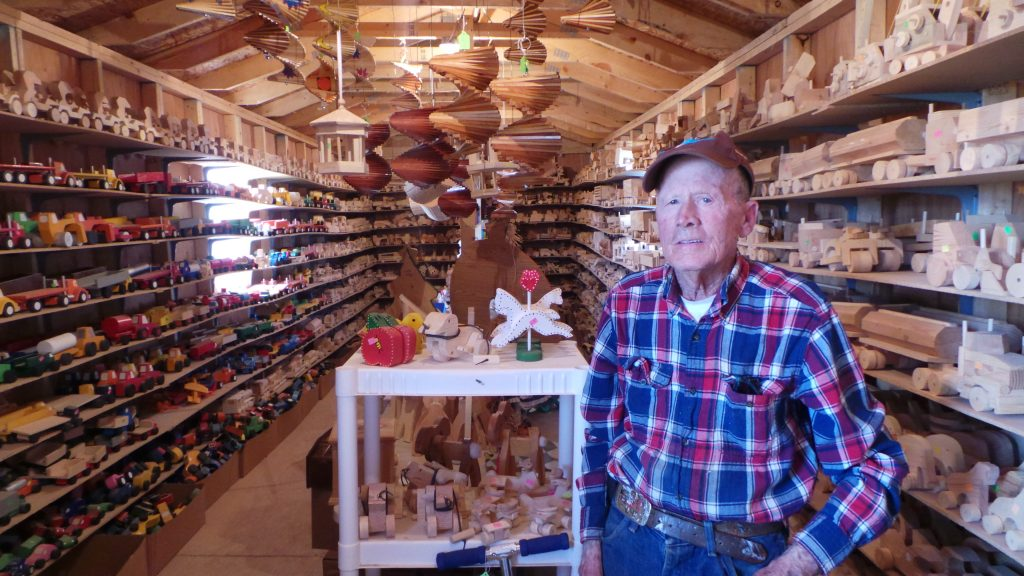 Elderly craftsman standing in shop with hundreds of wooden toys he's made