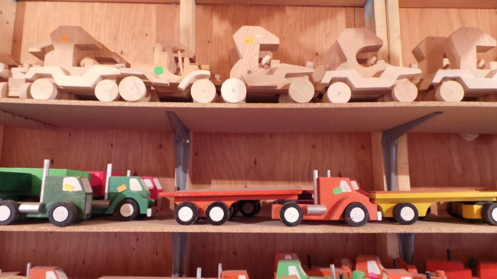 Assortment of unfinished Model-T cars on top shelf with smaller, painted semis on shelf below