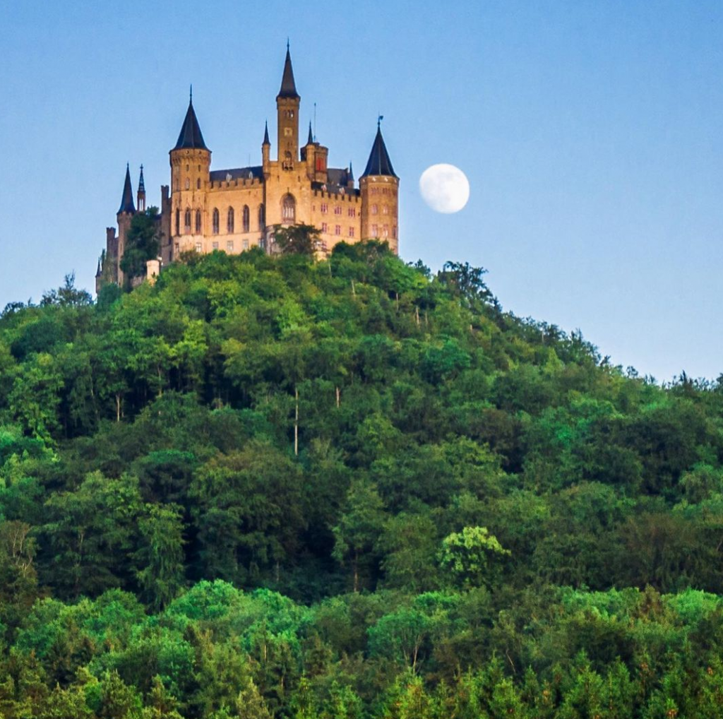 Picture of castle on a wooded hill with the moon in the background. Image by @waytogonate on Instagram